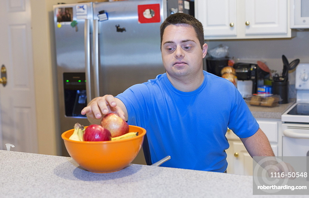 Man with Down Syndrome standing in kitchen holding fruits