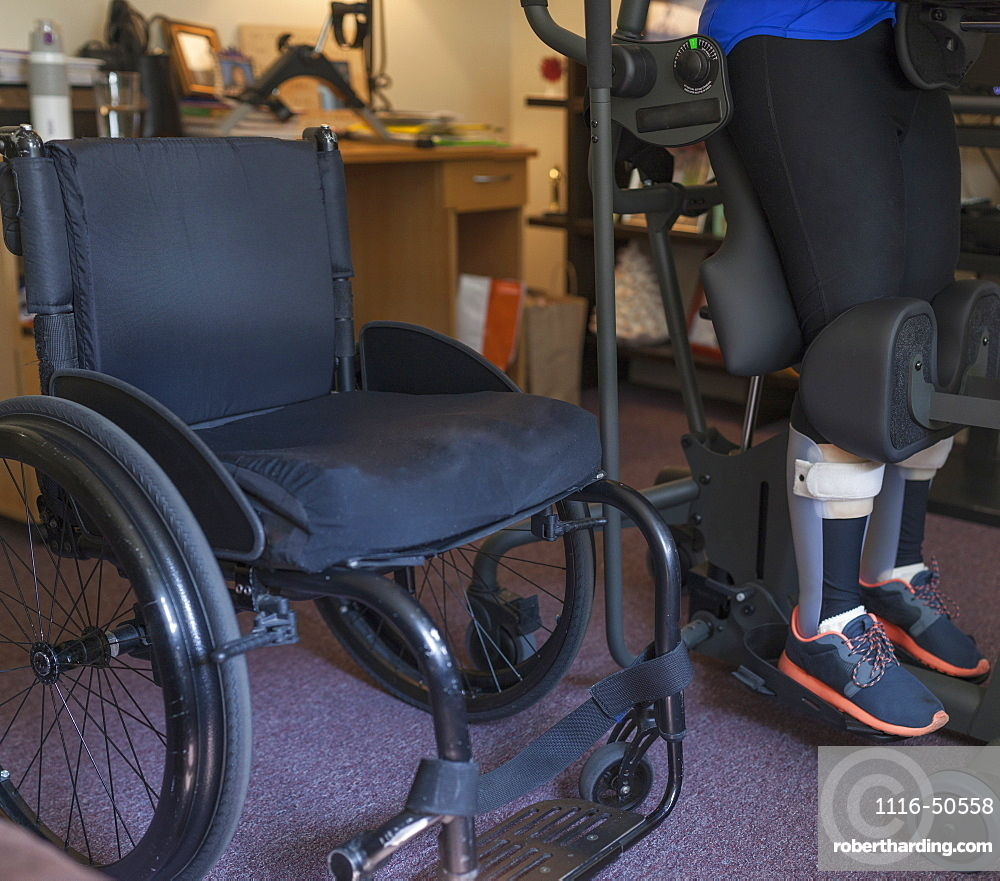Woman with spinal cord injury getting into her desk so she can stand up