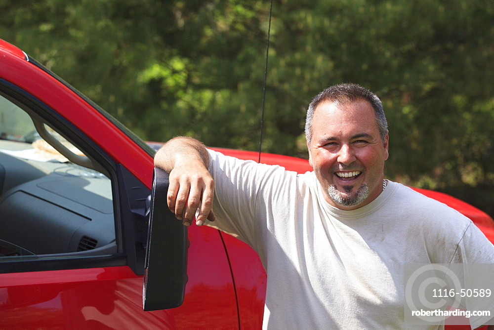 Landscaper smiling next to his truck