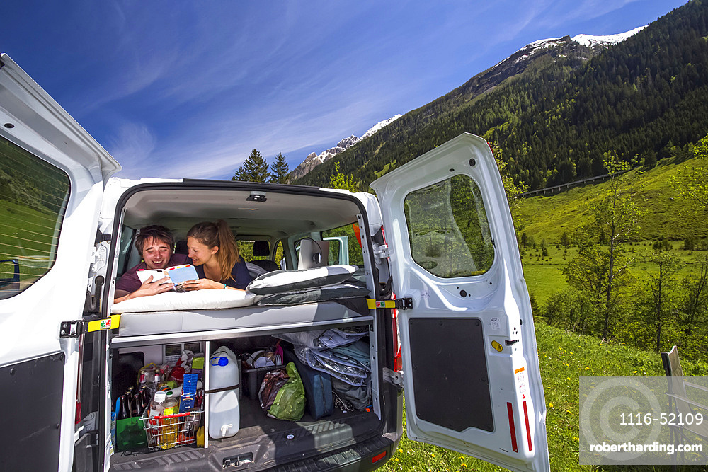 A couple takes a break and rests in the back of their campervan looking at their travel log at the base of the Alps before heading through Austria's highest mountain pass, the Grossglockner High Alpine Road; Austria