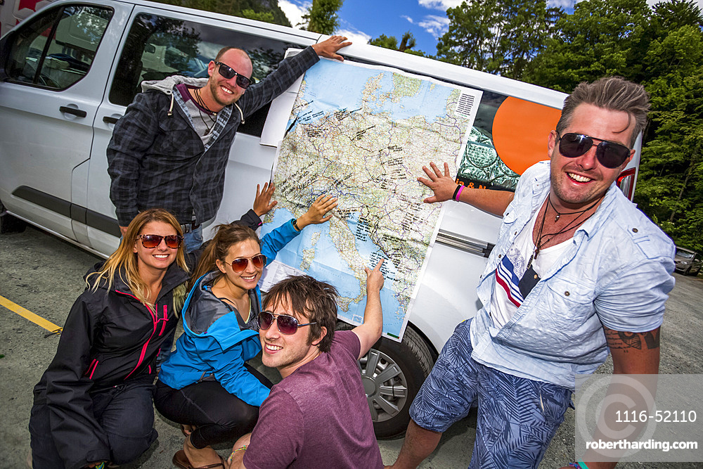 A group of travellers trace their trip on a map; Bled, Slovenia