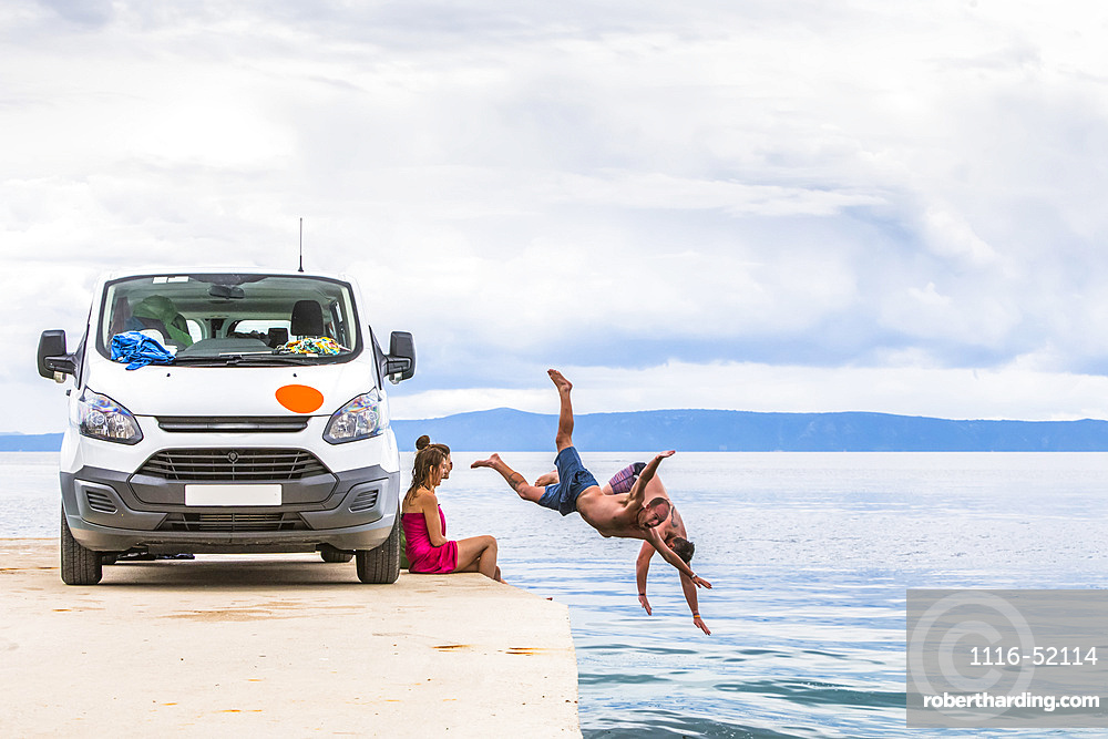 A group of travelers stop for an early morning swim in the ocean after camping in their van on a road trip; Podgora, Split-Dalmatia County (Splitsko-dalmatinska zupanija), Croatia