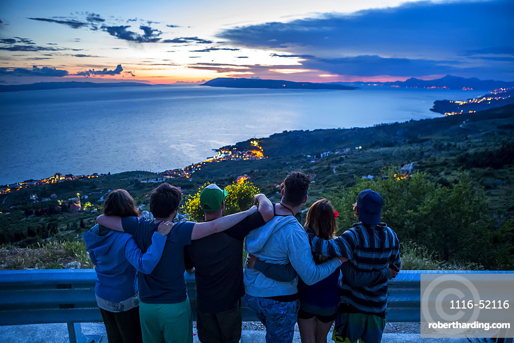 View taken from behind of travelers standing together with arms around each other enjoying a stop alongside the road to watch the sunset with The stunning high altitude cliffside views along the coastline of Croatia; Podgora, Dubrovnik-Neretva County (Splitsko-dalmatinska zupanija), Croatia