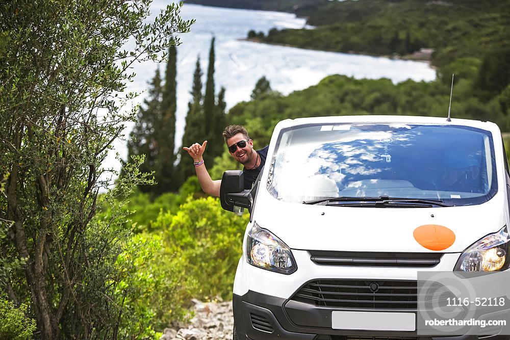 Man hanging out car window and driving camper van to find a secluded beach along the Croatia coastline; Zaton Doli, Dubrovnik-Neretva County (Dubrovacko-neretvanska zupanija), Croatia