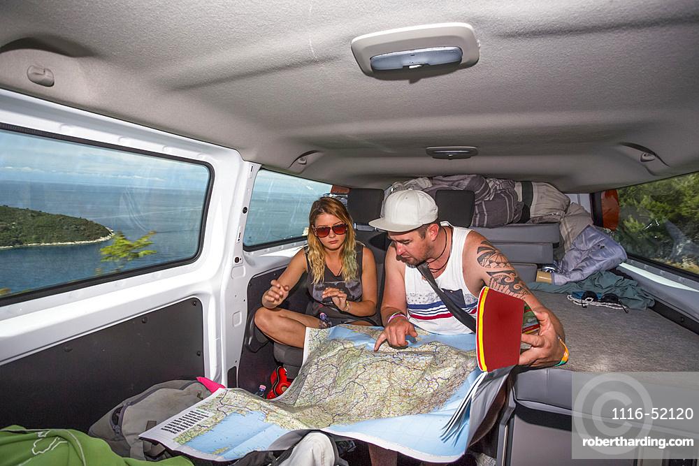 A couple looks over a map in their camper van with views over the city of Dubrovnik, Croatia; Dubrovnik, Dubrovacko-neretvanska zupanija, Croatia