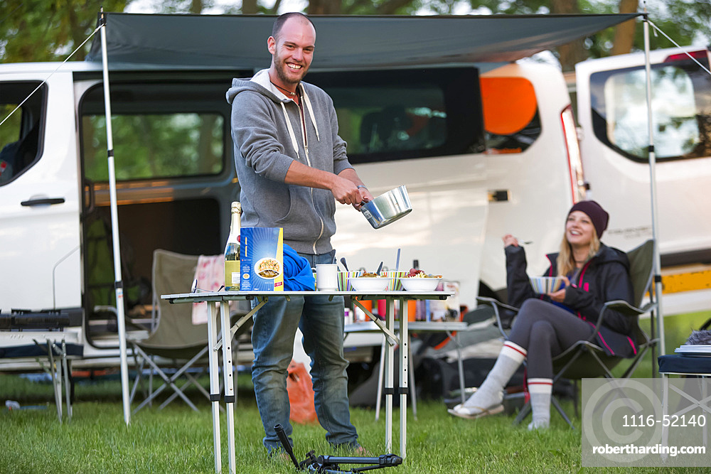 A stop for the night at a Czech Republic campsite between Prague and Cesky Krumlov. The 50 person town is called Kostelec and it is on the outsirts of Hluboka nad Vltavou. A camper prepares dinner for his friends; Kostelec, Vltavou, Czech Republic