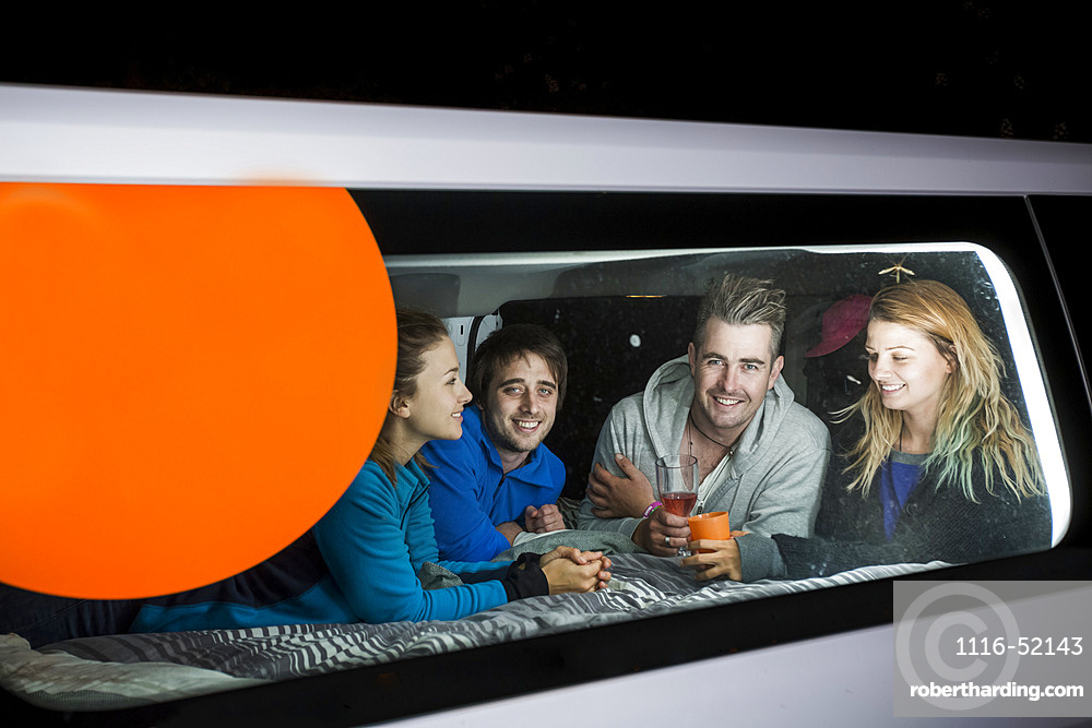 A group free camps for the evening in the German city of Kassel. The group huddles inside the van to play games; Kassel, Kassel, Germany