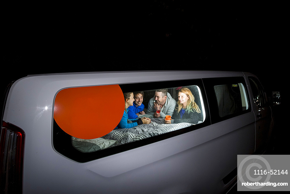 Group of travelers huddled inside their camper van playing games for the evening, free camping in the German city of Kassel; Kassel, Germany