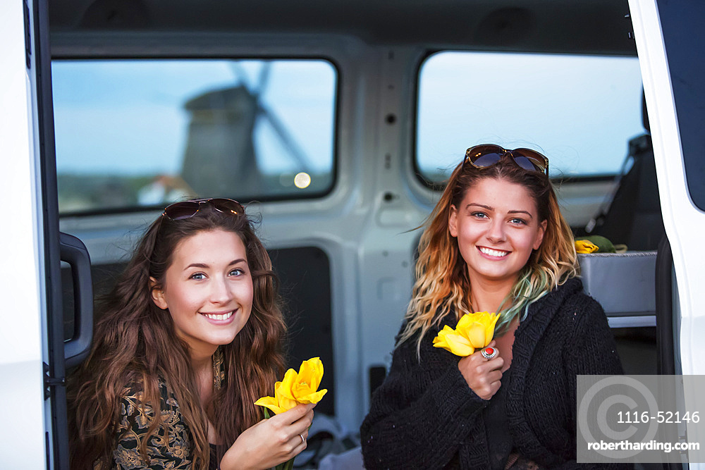 Two young women sit in a vehicle holiday fresh-picked yellow tulips. A journey outside of Amsterdam central leads to the coastal city of Egmond aan Zee. Travellers go out in search of Holland's famous windmills; Egmond aan Zee, Holland