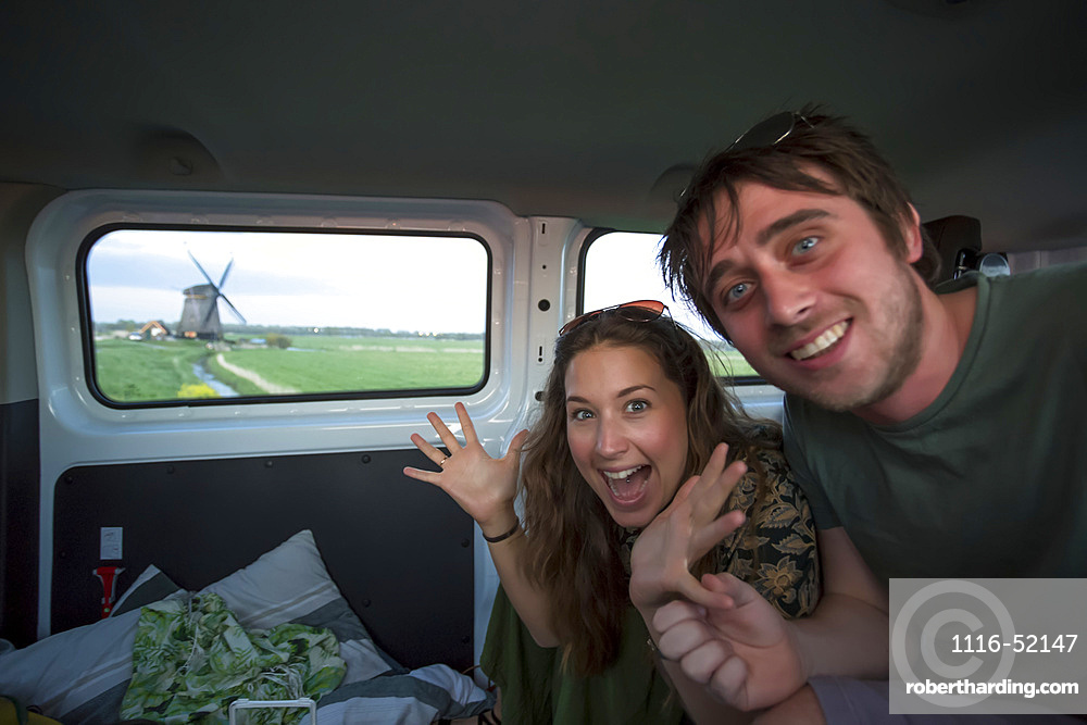 Travelers inside a camper van exploring North Holland searching for iconic windmills outside of Amsterdam Central along the journey to the coastal city of Egmond aan Zee; Holland
