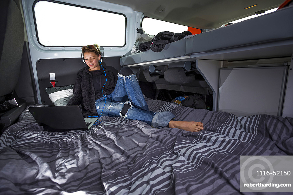 The inside of a campervan becomes a work station and living room. A young woman relaxed with a laptop and headphones; Penzance, England, United Kingdom