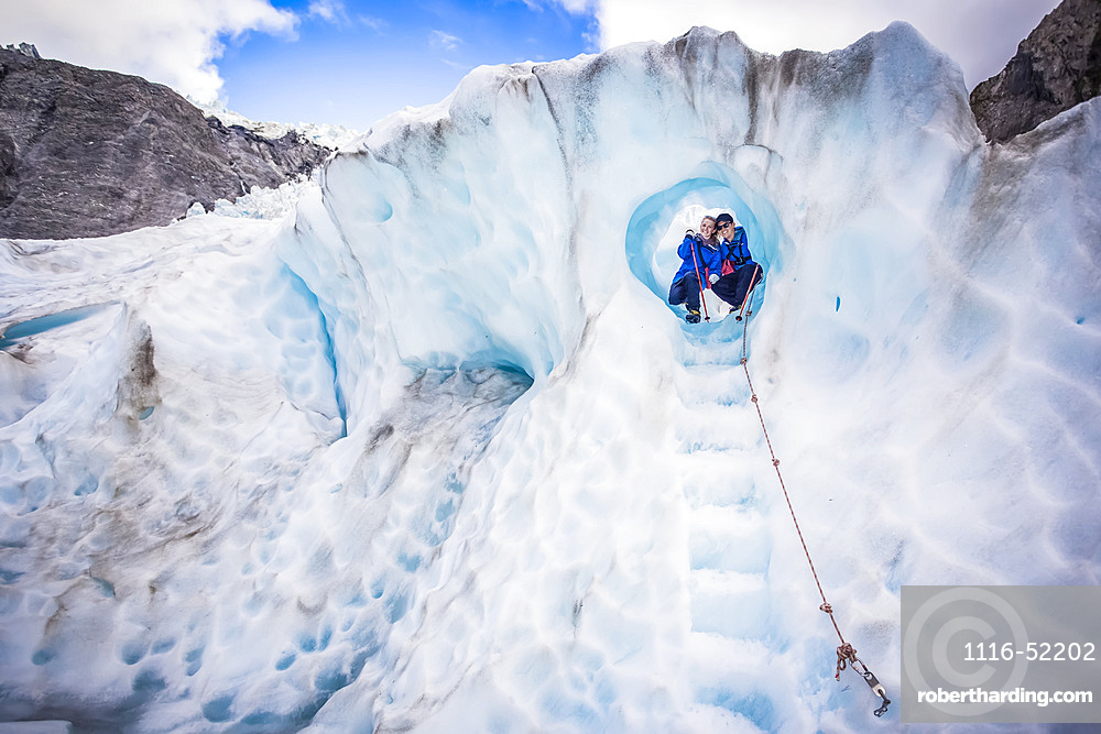 Travellers explore New Zealand's famous Franz Josef Glacier. Blue Ice, deep crevasses, caves and tunnels mark the ever changing ice; West Coast, New Zealand