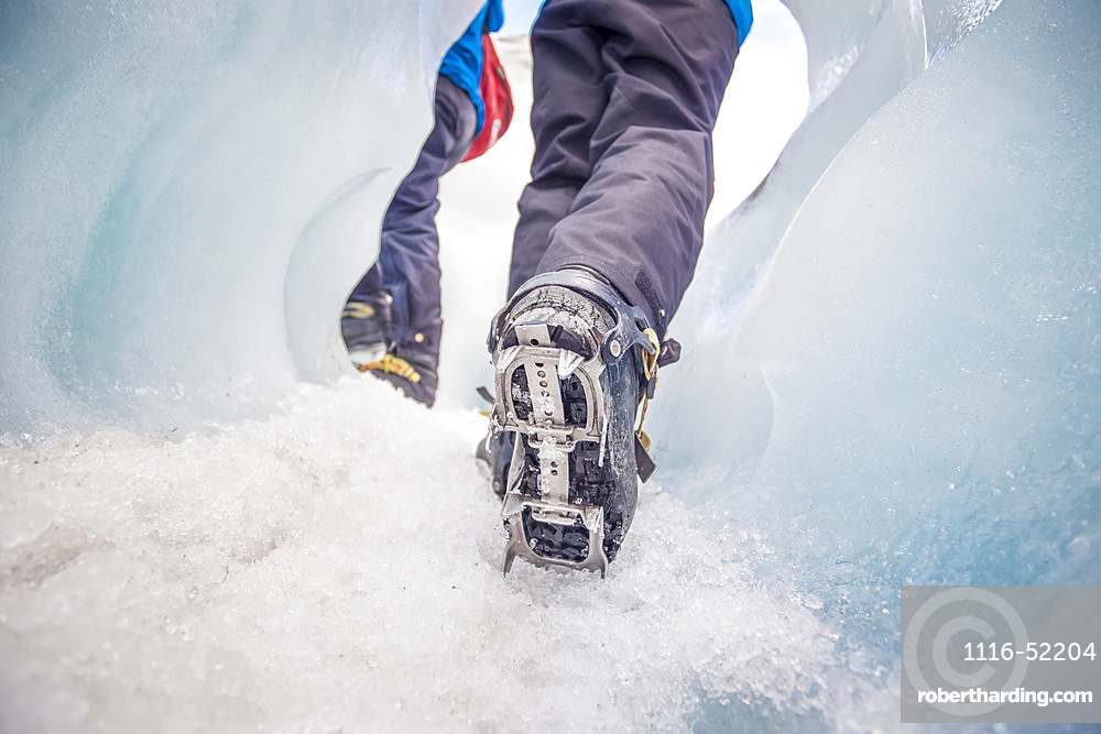 Close-up of person's feet wearing spiked traction cleats while walking on ice through the famous Franz Josef Glacier; West Coast, New Zealand