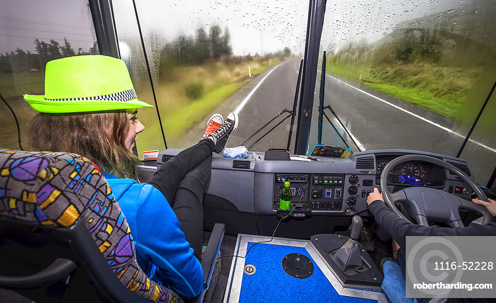 A girl sits in the front seat of a bus as they travel through New Zealand, Tongariro National Park; Manawatu-Wanganui, New Zealand