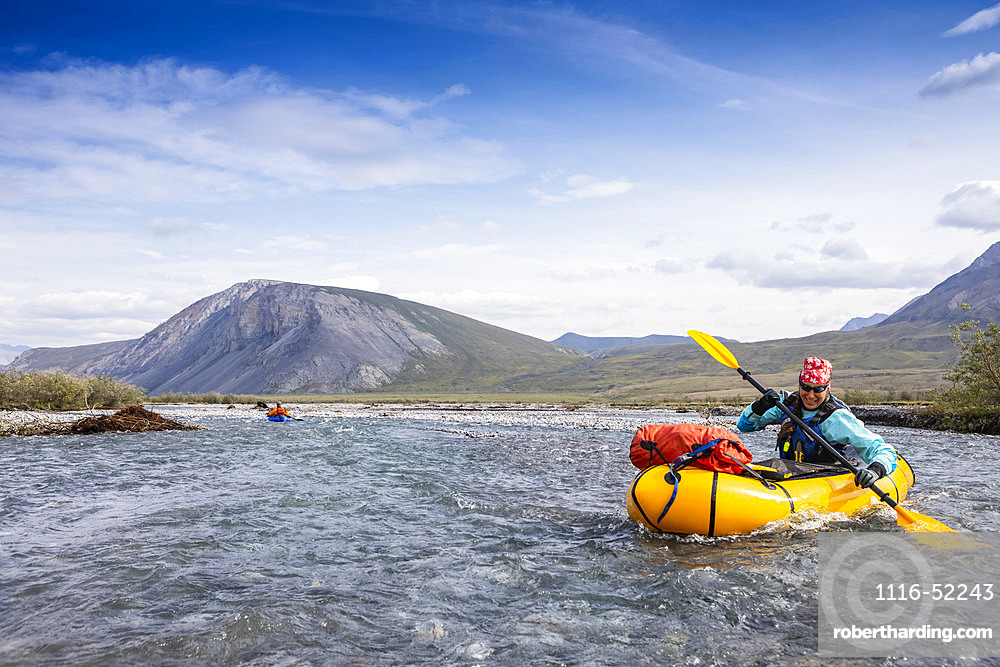 Caucasian woman in her 40's smiles as she digs deep with her paddle into the river, guiding her yellow packraft down the crystal clear Marsh Fork River, in the Brooks Range, on a sunny summer day, Arctic National Wildlife Refuge, Alaska, while another boat is in the background way behind her; Alaska, United States of America