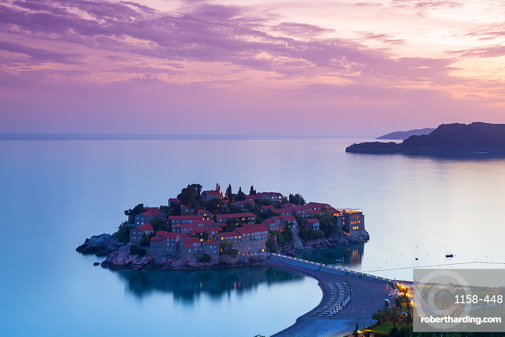 Elevated view over the picturesque island of Sveti Stephan illuminated at dusk, Sveti Stephan, Montenegro, Europe