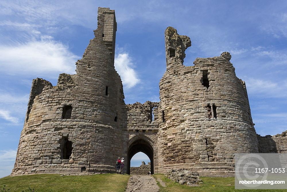 Walkers arrive at historic Dunstanburgh Castle, Northumberland, England, United Kingdom, Europe