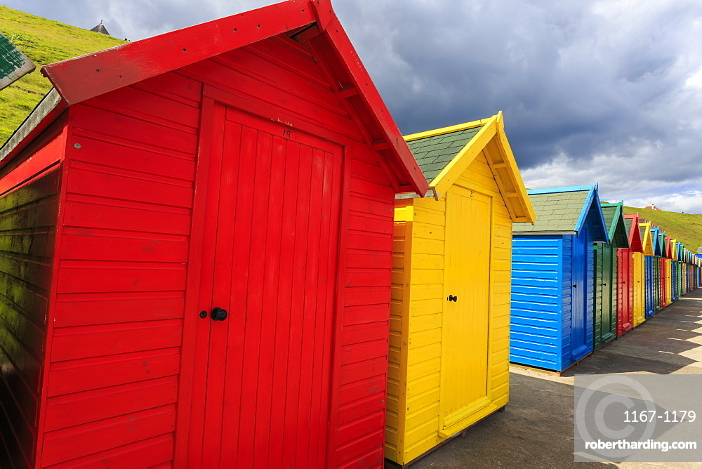 Row of colourful beach huts and their shadows, with grassy cliffs, West Cliff Beach, Whitby, North Yorkshire, England, United Kingdom, Europe