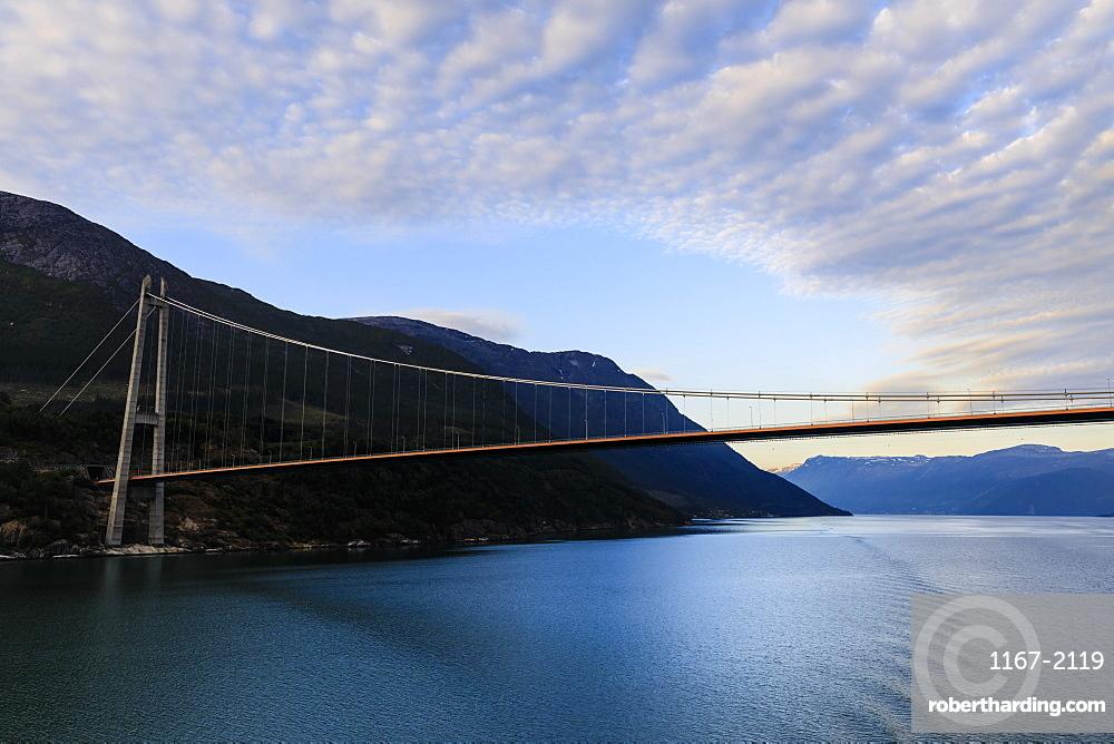 Passing under the huge Hardanger Bridge, sunrise, beautiful dawn clouds, Hardangerfjord, Norwegian Western Fjords, Norway, Scandinavia, Europe