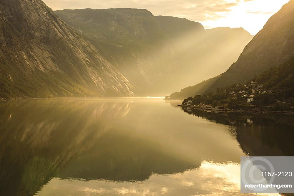 Shafts of light enter misty, beautiful Eidfjord, fjord reflections, Hardangerfjord, Norwegian Western Fjords, Norway, Scandinavia, Europe