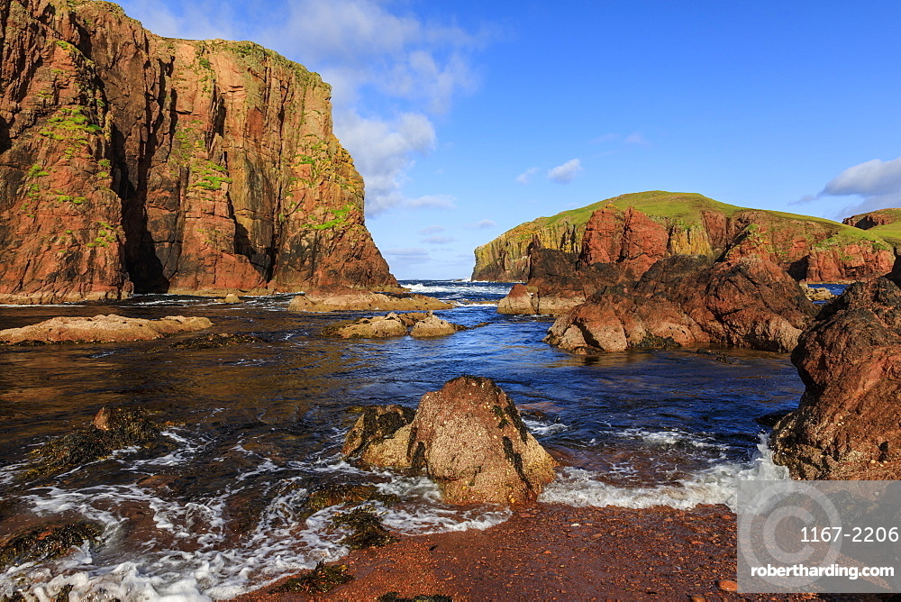 North Ham Bay, deep inlet, lichen covered red granite cliffs and stacks, seaweed, Muckle Roe Island, Shetland Isles, Scotland