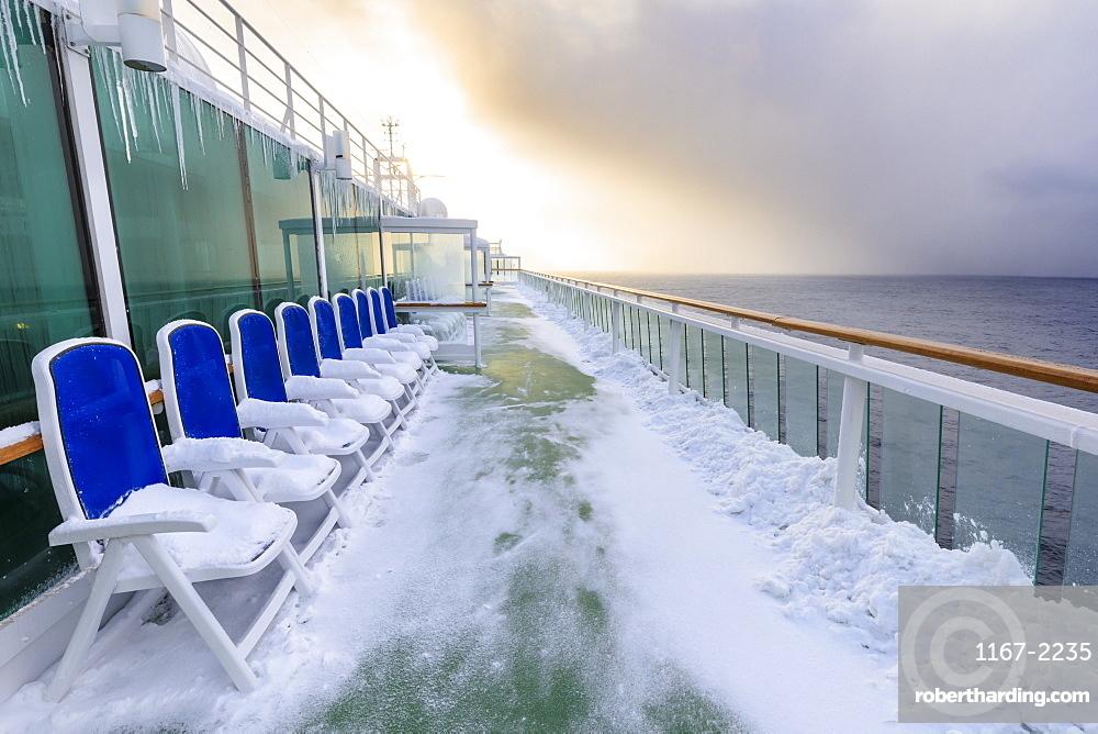 Cruise ship on an Arctic Winter voyage, fresh powder snow on decks, off Troms County, North Norway, Scandinavia, Europe