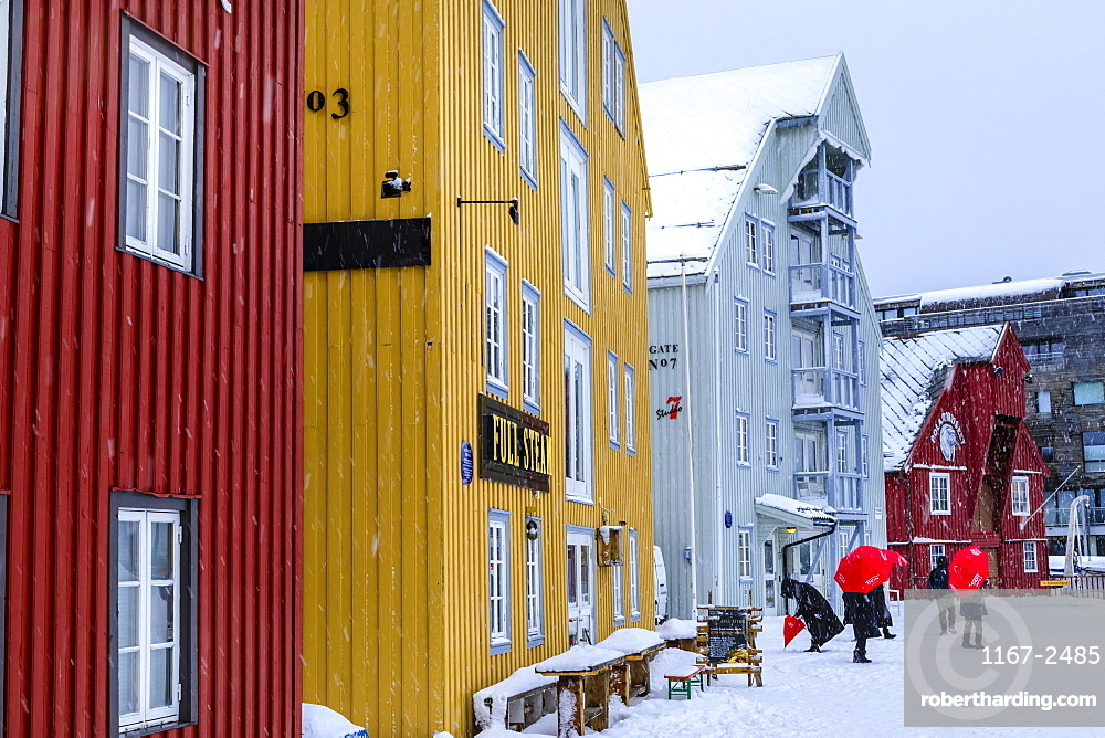 Tromso, tourists, colourful historic wooden buildings, heavy snow, Winter, Troms og Finnmark, Arctic Circle, North Norway