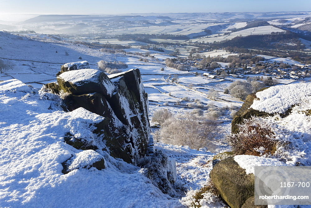 Snowy Curbar village beyond the rocks of Curbar Edge, winter morning, Peak District National Park, Derbyshire, England, United Kingdom, Europe
