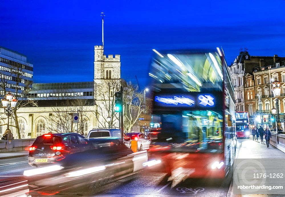 UK, London. A London double-decker bus in moving traffic on Putney Bridge in the early evening
