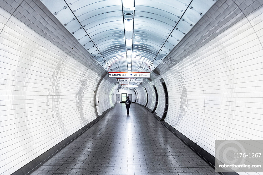 UK, London. A single person walking along a corridor in an underground station during the Coronavirus lockdown