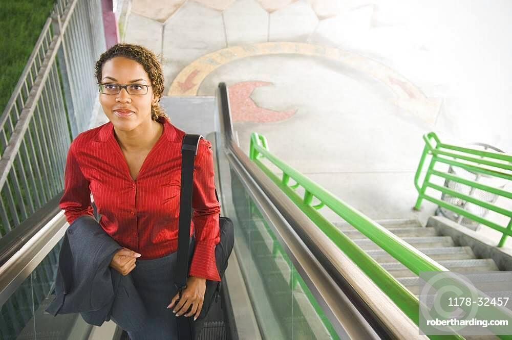 African businesswoman on escalator
