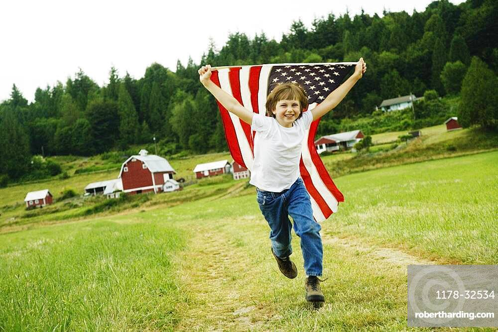 Boy running with American flag at farm