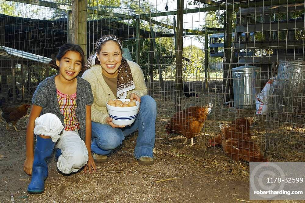 Hispanic mother and daughter with bowl of eggs next to chickens