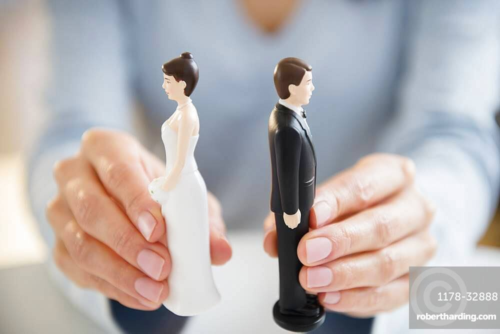 Hands holding bride and groom cake toppers