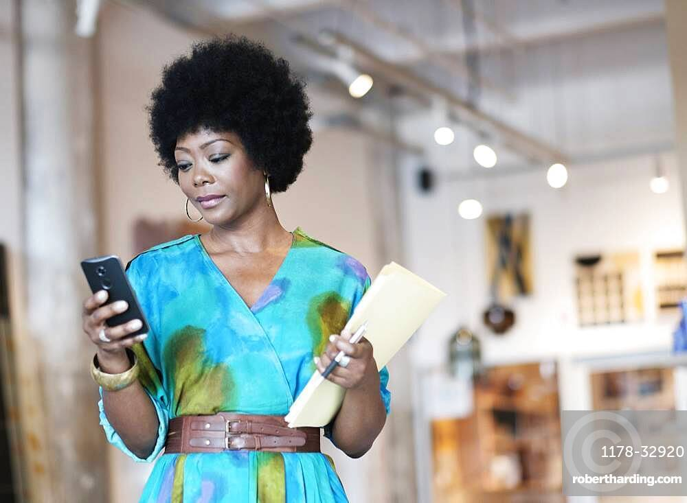 African American business owner using cell phone in store