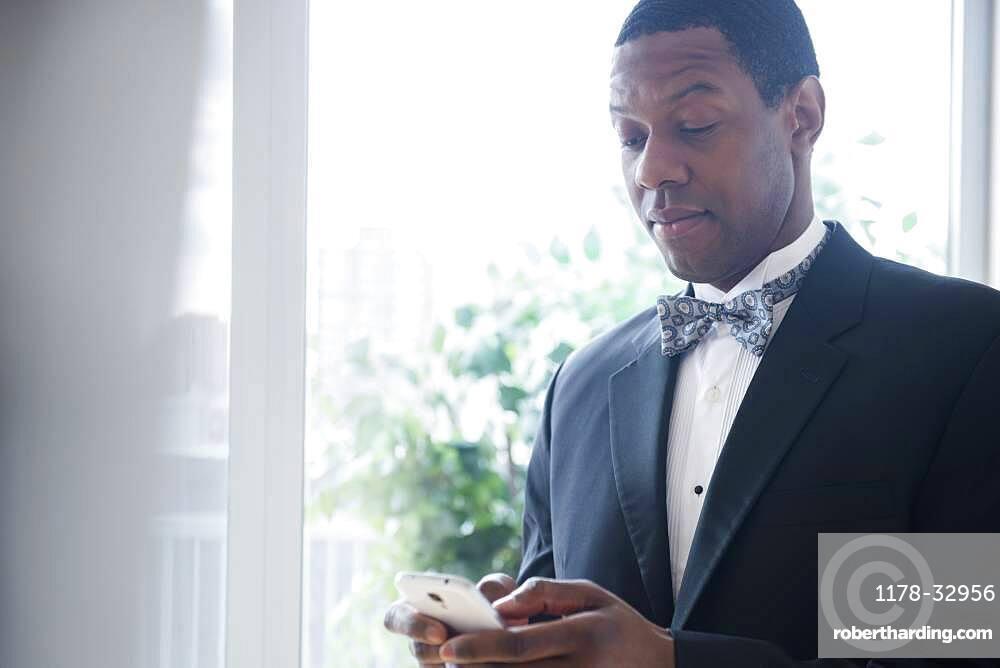 Groom in tuxedo using cell phone