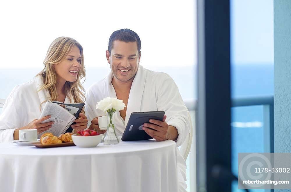 Couple enjoying breakfast on balcony