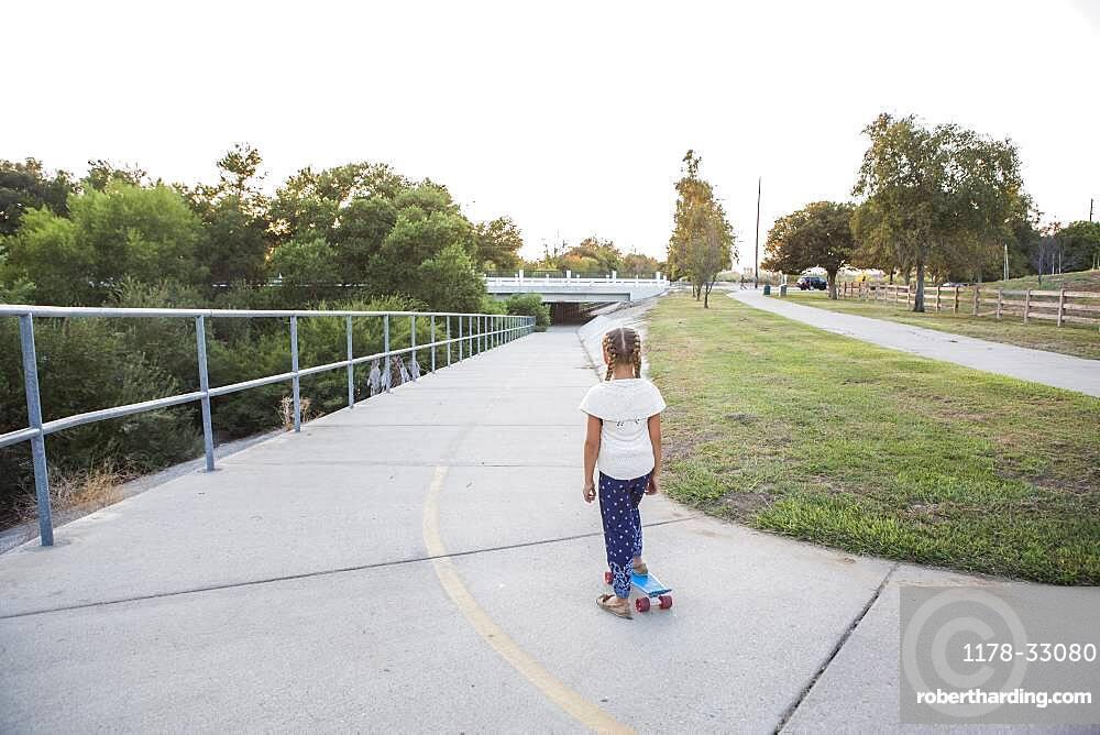 Mixed race girl riding skateboard in park