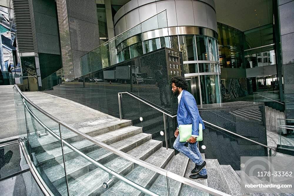 Mixed race businessman carrying digital tablet