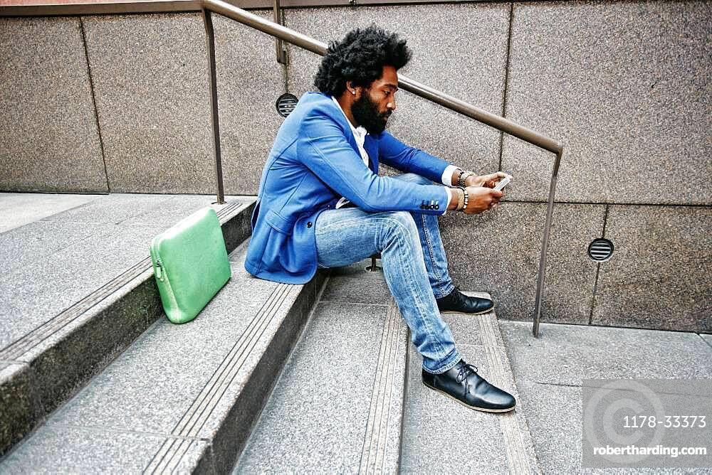 Mixed race businessman using cell phone
