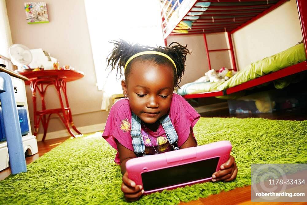 Black girl using digital tablet in bedroom
