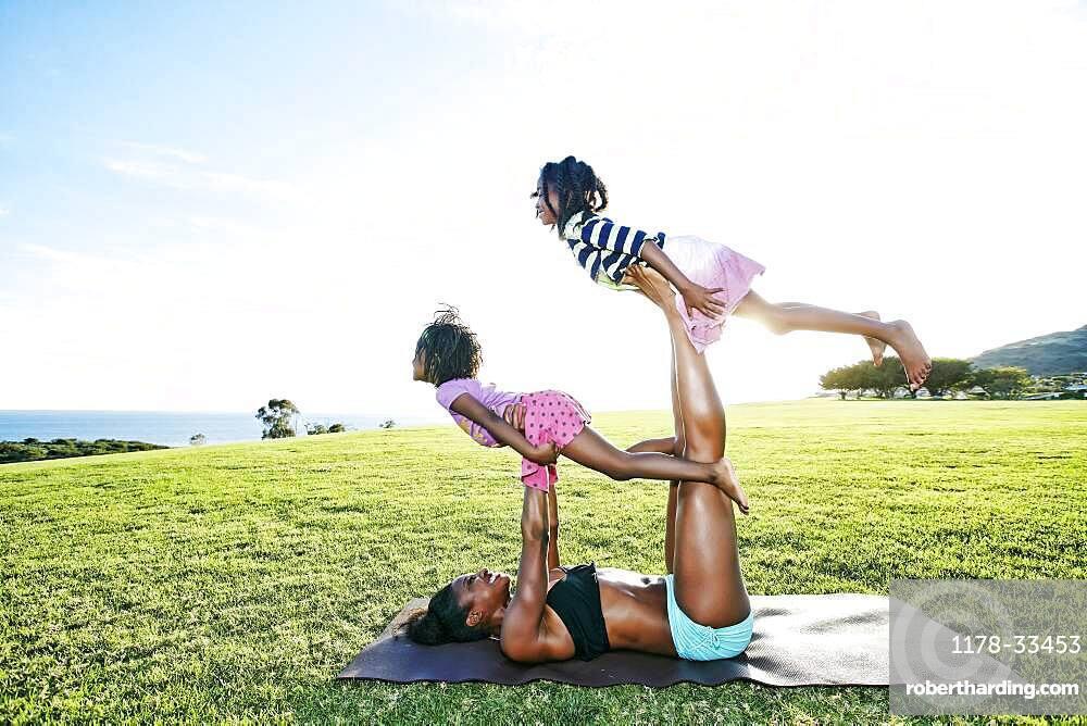 Mother holding children on yoga mat in park