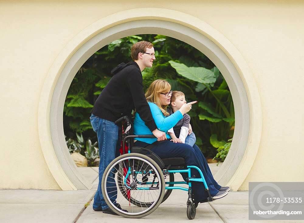 Man pushing paraplegic wife and son