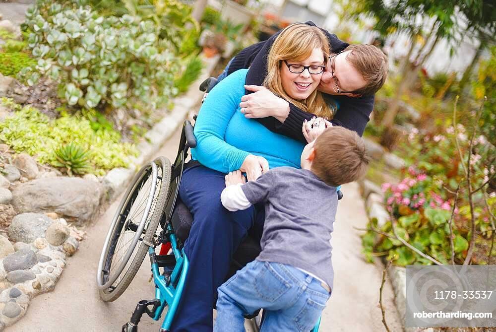 Paraplegic woman and family hugging in garden
