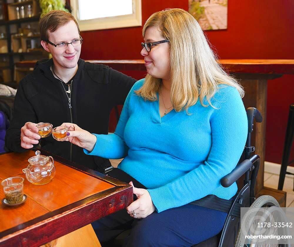 Paraplegic woman and boyfriend drinking tea