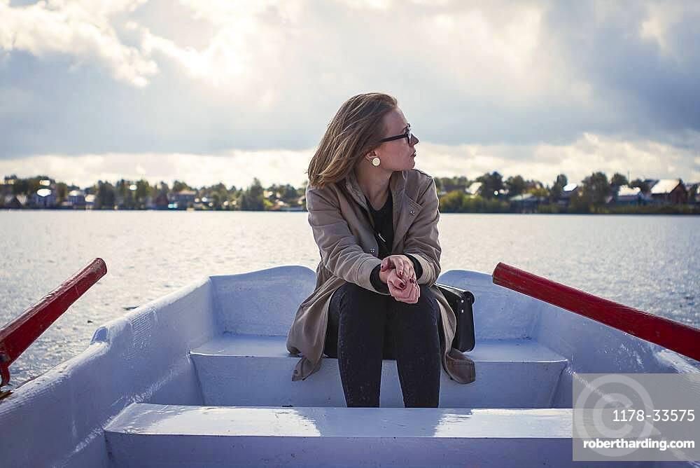 Caucasian woman sitting in rowboat