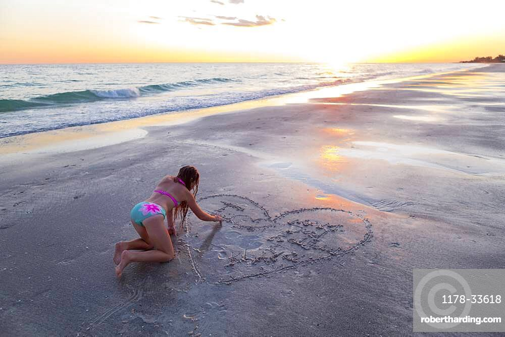 Caucasian girl drawing in sand on beach