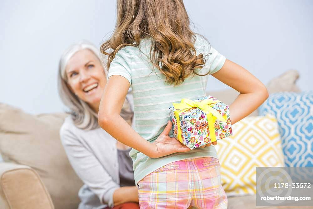 Caucasian girl hiding gift for grandmother behind back