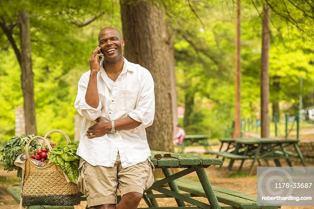 African American man talking on cell phone on picnic table