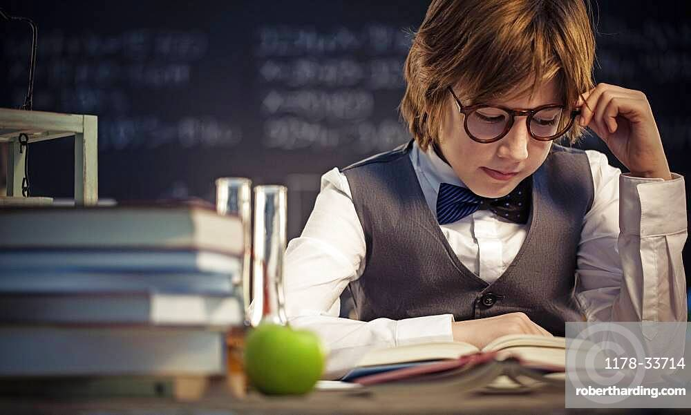 Student reading book at desk in classroom
